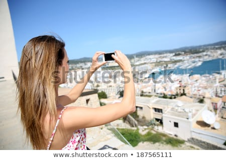 Ibiza girl taking smartphone photos Stock photo © lunamarina