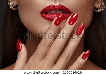 Beauty model. Manicured hand with red nails. Red lips and nails Stock photo © serdechny