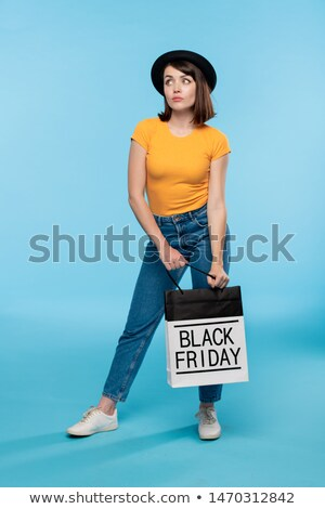 Young brunette female in black hat, jeans and t-shirt standing in isolation Stock photo © pressmaster