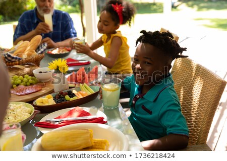 Side view of a multi-generation African American family eating dinner together on dining table at ho Stock photo © wavebreak_media