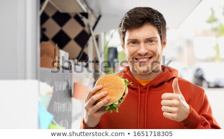 happy young man with hamburger showing thumbs up Stock photo © dolgachov