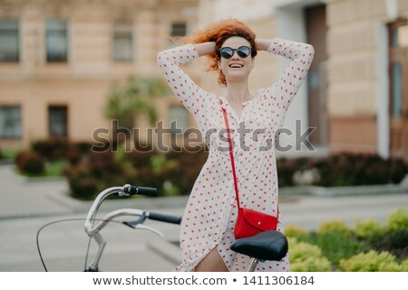 Smiling woman rides bike in city, keeps hands behind on head, feels freedom, wears sunglasses and su Stock photo © vkstudio