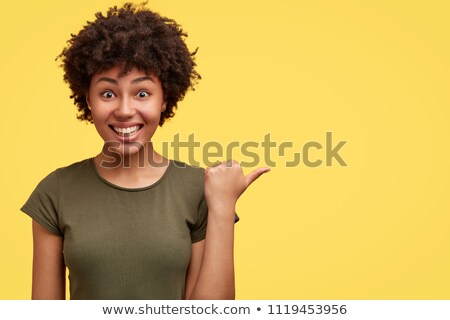 Emotional glad African American woman with crisp black hair, raises hands, gestures actively, observ Stock photo © vkstudio