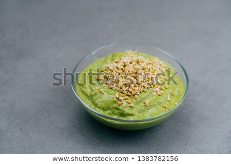 Bowl of green smoothie made of spinach with buckwheat sprouts on grey background. Vegan food. Health Stock photo © vkstudio