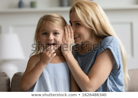 daughter whispering secret to mother at home Stock photo © dolgachov