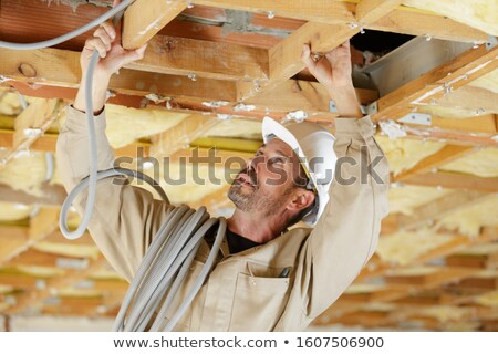 Plumber holding a blue pipe above a ceiling Stock photo © photography33
