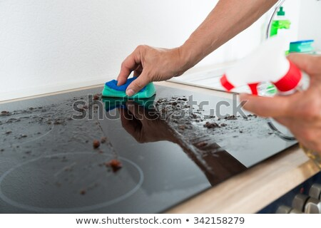 person hand cleaning induction stove stock photo © andreypopov