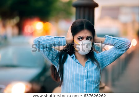 Girl With Mask Covering her Ears Because of Noise Pollution Stock photo © NicoletaIonescu