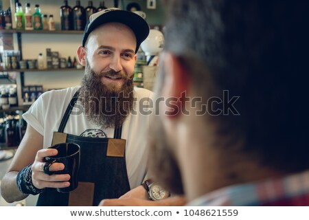 Dedicated hairstylist drinking coffee with his customer and friend Stock photo © Kzenon