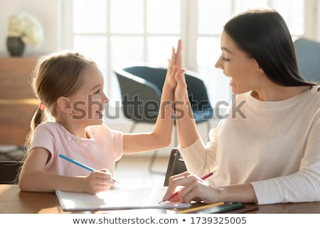 Mother and daughter working together giving high-five Stock photo © Kzenon