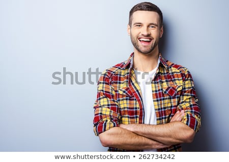 Portret uśmiechnięty młody człowiek stałego odizolowany beżowy Zdjęcia stock © deandrobot