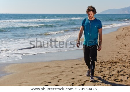 Sportsman walking outdoors on the beach listening music with earphones. Stock photo © deandrobot