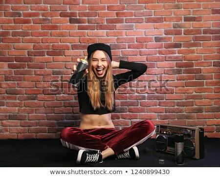 Photo of modern hip hop girl, sitting on floor against brick wal Stock photo © deandrobot