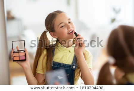 portrait of girl putting lipstick on her lips and looking in mirror stock photo © studiolucky
