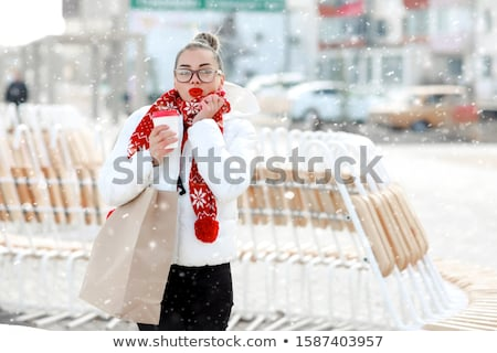 Smilling winter girl in knitted warm hat and mittens holding a cup in hands. Stock photo © ElenaBatkova