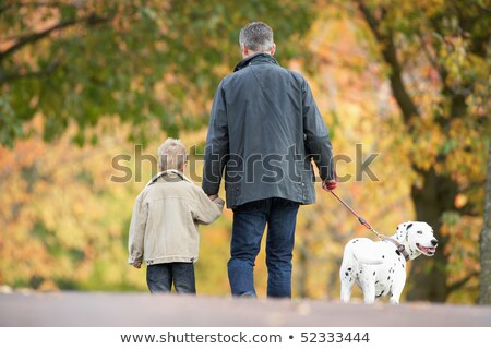 Man With Young Son Walking Dog Through Autumn Park Stock photo © monkey_business