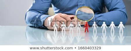 human hand holding magnifying glass over red human figures stock photo © andreypopov