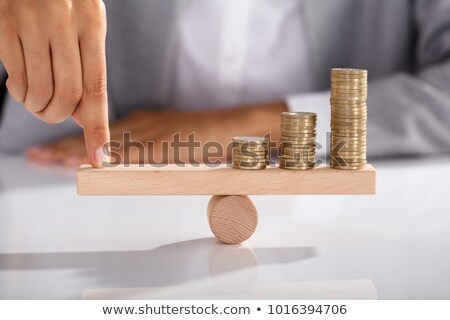Balancing Stacked Of Golden Coins On Wooden Seesaw Stock photo © AndreyPopov