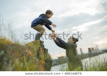 Mother Helping Children To Jump Off Rocks Foto stock © Lopolo