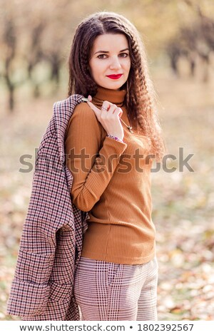 Young business lady holding coat over her shoulders Stock photo © stockyimages