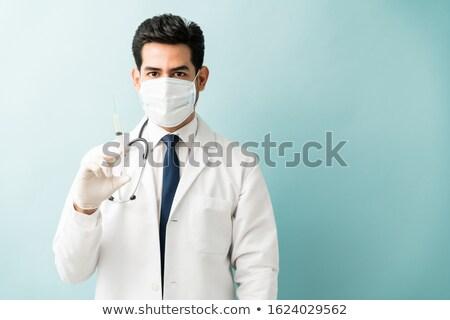 Young hispanic doctor holding syringe. Stock photo © RAStudio