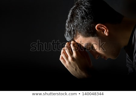 side view of a young man praying with eyes closed stock photo © feedough