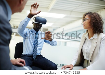 Young businessman with vr goggle watching virtual presentation Stock photo © pressmaster