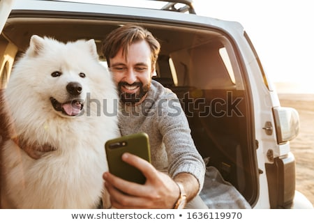 Man with dog samoyed outdoors at the beach Stock photo © deandrobot