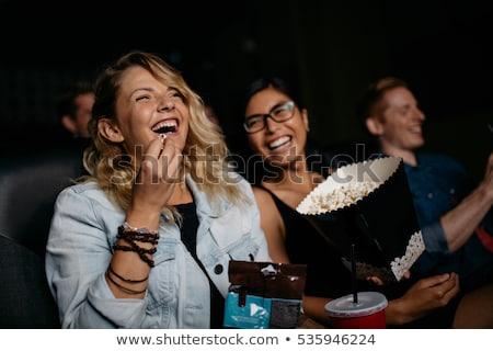 улыбаясь девушки еды попкорн фильма театра Сток-фото © dolgachov