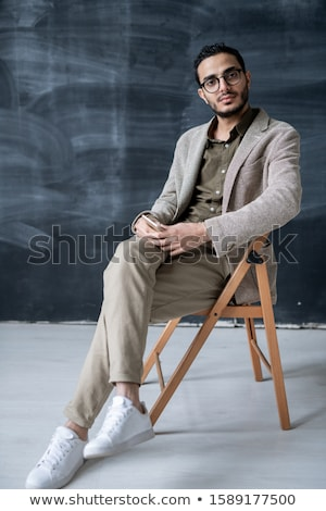 Indoor shot of serious confident businessman poses in chair, poses at cabinet, waits for colleagues  Stock photo © vkstudio