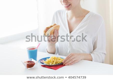 Közelkép nő eszik hotdog sültkrumpli ünnepek Stock fotó © dolgachov