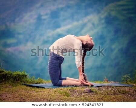Woman doing yoga asana Ustrasana camel pose outdoors Stock photo © dmitry_rukhlenko