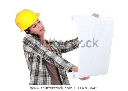 Stock photo: craftswoman examining an architectural plan