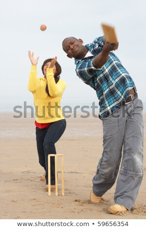young couple playing cricket on autumn beach holiday stock photo © monkey_business
