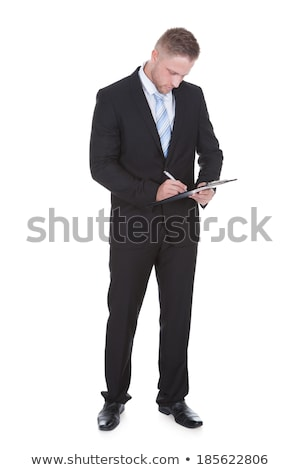 businessman standing writing on a handheld clipboard stock photo © andreypopov