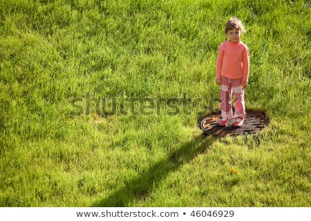 Stock photo: Little girl is standing and frowning on water drain hatch in grass field.
