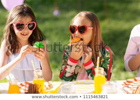 Young girl at party sitting at table with a cupcake smiling Stock photo © monkey_business