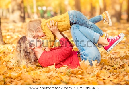 young boy lying on autumn leaves stock photo © is2