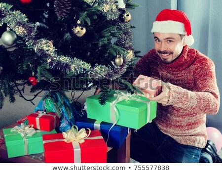 Férfi rejtőzködik ajándékok karácsonyfa karácsony boldogság Stock fotó © IS2