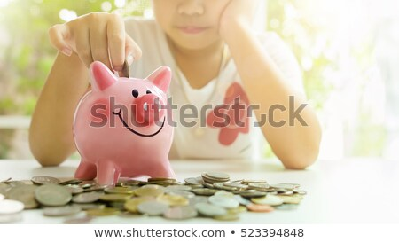 Girl with piggy bank and piles of money Stock photo © IS2