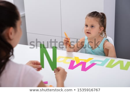 a young girl is sitting on a table in the office holding a pen and a tablet with sheets and scratch stock photo © traimak