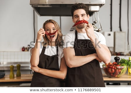 Friends loving couple chefs standing on the kitchen holding cake. Stock photo © deandrobot