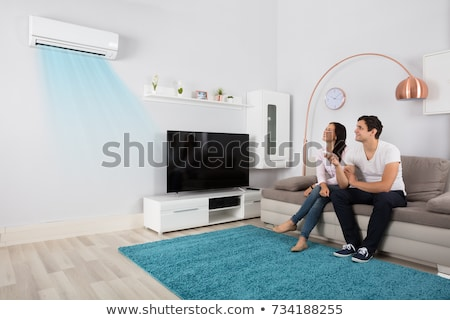 happy couple operating air conditioner at home stock photo © andreypopov