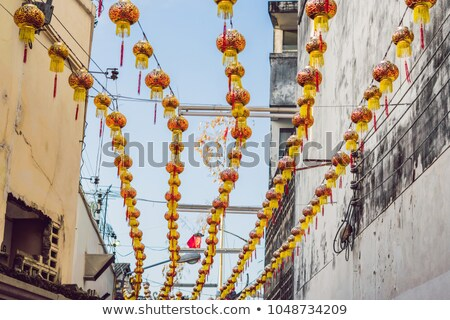 Red Chinese lanterns hang between houses during the day Stock photo © galitskaya