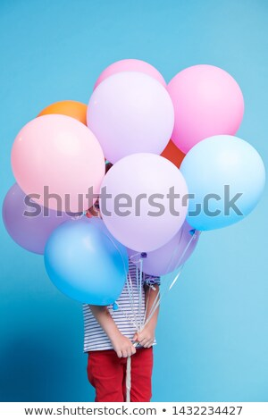 Stock photo: Casual little girl peeking through small hole between colorful balloons