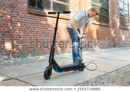 Man Pumping Air Into Tire On E-Scooter Stock photo © AndreyPopov