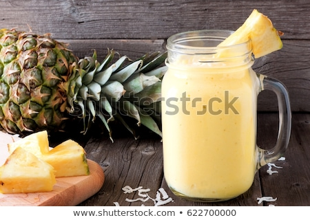 Pineapple and pineapple smoothies on an old wooden background Stock photo © galitskaya