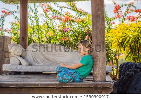 Cute boy listens to music in a Buddhist temple Stock photo © galitskaya