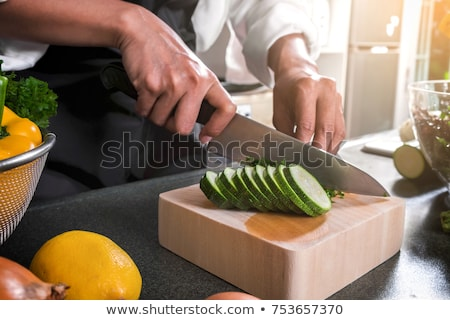 Close up of woman hand cutting tomato on chopping wood board wit Stock photo © Freedomz