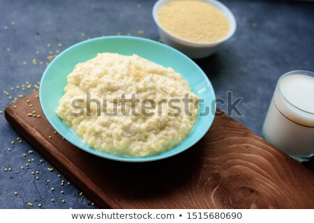Millet in wooden bowl isolated. Groats in wood dish. Grain on wh Stock photo © MaryValery